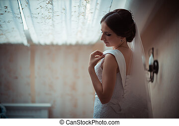 Portrait of a beautiful bride in the matrimonial bedroom