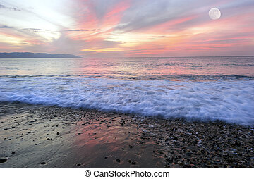 Ocean Sunset - Beach sunset is a colorful vivid red and...