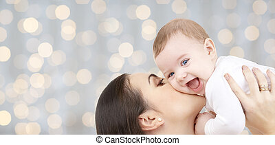 happy mother kissing her baby over lights - family,...