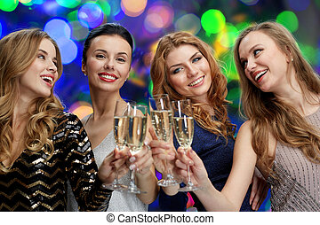 happy women clinking champagne glasses over lights -...