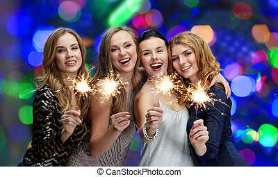 happy young women with sparklers over lights - party,...