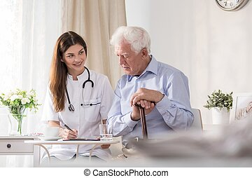 Patient talking to community nurse - Elderly patient talking...
