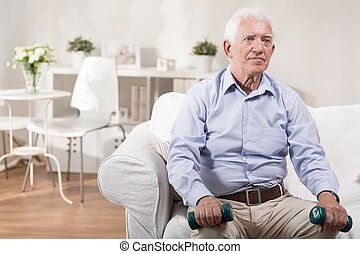 Elderly man sitting with dummbells
