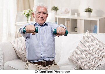 Elderly man exercising at home - Elderly man exercising with...