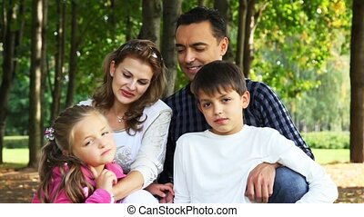 family with boy and girl sits in park, looks against each other and smiles