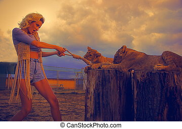 sexy woman playing with lion cub on background with...