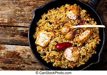 pilaf in a pig-iron frying pan top view style rustic...