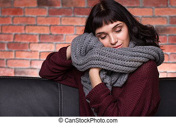 Beautiful smiling young woman enjoying new gray soft knitted...