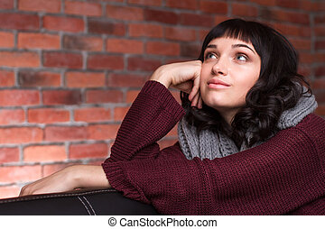 Lovely cute young woman in knitted clothes sitting and...