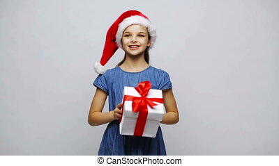 happy smiling girl in santa hat shaking gift box -...