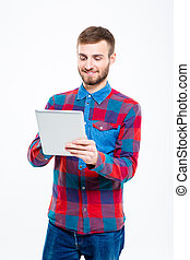Content smiling attractive man in plaid shirt using tablet...