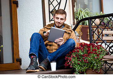 Smiling bearded man sitting on porch near entrance using...