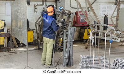 welder working with electrode at semi-automatic arc welding...