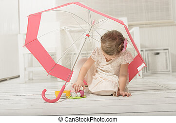 Little girl playing under umbrella - Lovely little girl...