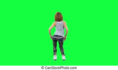 Dancing woman isolated on green - Girl dancing twerk against...