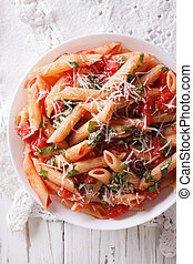 Arrabiata pasta penne with Parmesan cheese closeup. vertical...