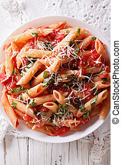 Hot pasta arrabbiata closeup on a plate vertical top view -...