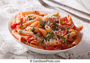 Hot pasta arrabbiata with parmesan and herbs closeup...