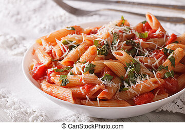 arrabbiata pasta with parmesan and herbs closeup on a plate...