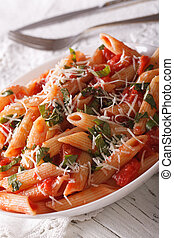 arrabbiata pasta with Parmesan cheese on a plate closeup...