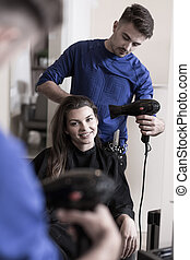 Professional male hairdresser with professional hair dryer