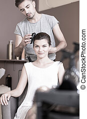 Doing elegant hairstyle - Beautiful brunette woman and...
