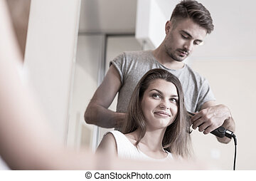 Using hair straightener - Hairdresser using hair...