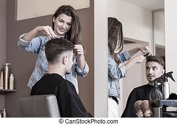 Young female hairdresser cutting male clients hair
