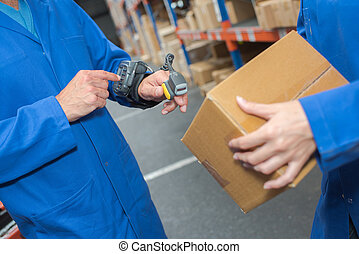Man in warehouse using hand held scanner