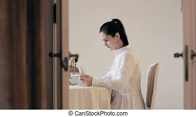 Woman using tablet and drinking coffee by table - Woman...