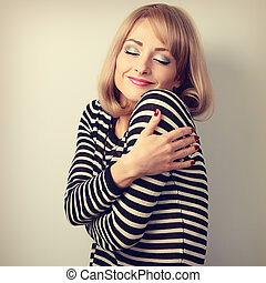 Happy makeup blond woman hugging herself with natural...