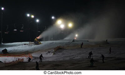 Skiers ride on the ski slopes and snow cannons - Many skiers...