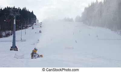 Skiers ride on the ski slopes and snow cannons.