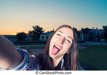 Young funny girl is making selfie having fun with her tongue...