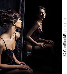 Beautiful seductive girl sitting in armchair with a mirror...