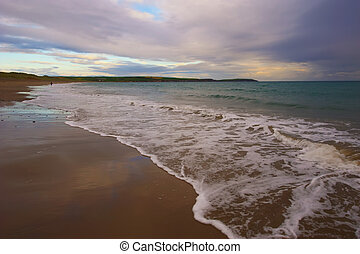 Lonley Beach - waves break gently on beach in Co.Cork,...