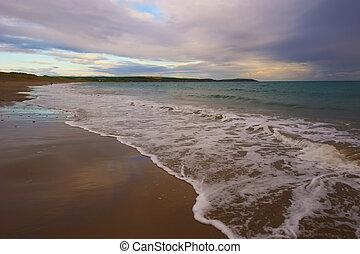 Lonley Beach - waves break gently on beach in CoCork,...
