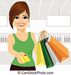 young woman holding shopping bags and giving a credit card -...