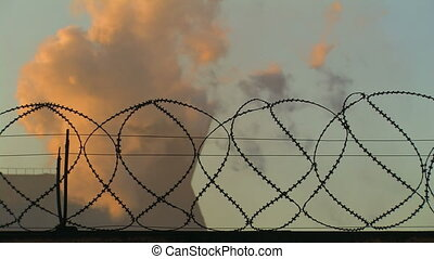 Smoking Chimney behind Barbed Wire - Smoking Chimneys behind...