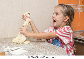 Cheerful girl tears off a piece of dough