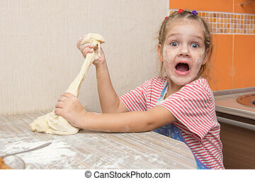 The girl tears off a piece of dough for pies and happily looks into the frame