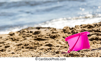 Small sand pail toy on summer beach Holiday vacation