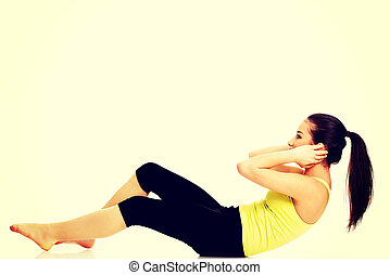 Woman exercising and doing a crunch - Woman exercising and...