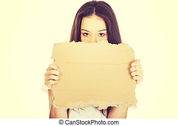 Young woman holding a cardboard. - Teenage woman holding...