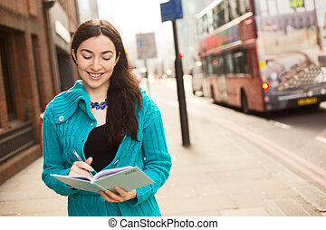 diary - happy young woman writing in a book in the street