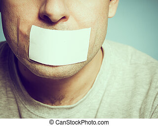 Caucasian man with duct tape on mouth, white Conceptual...