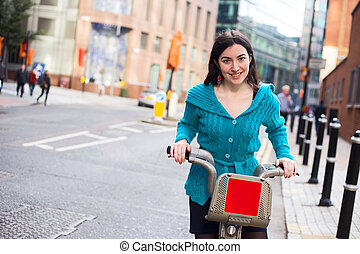 hire bike - young woman riding a hire bike in the street