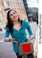 london cyclist - a happy girl riding a hire bike