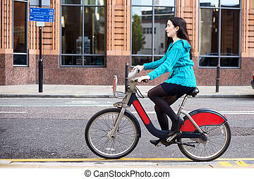 cyclist - young woman riding a hire bike in the street