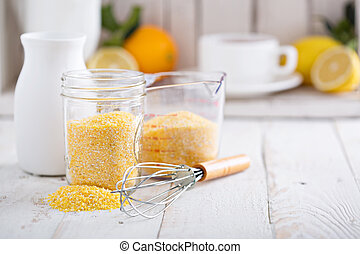 Raw cornmeal with a whisk - Raw cornmeal in a jar and...
